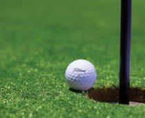 balle à côté d'un trou de golf